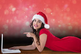 Composite image of festive brunette lying pointing her laptop  — Stock Photo