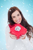 Brunette showing red gift with bow — Stock Photo