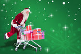 Santa pushes shopping cart — Stock Photo