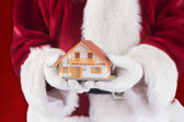 Santa holds a tiny house — Stock Photo