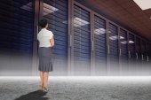 Businesswoman standing against server hallway — Stock Photo