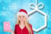 Composite image of festive blonde holding a gift bag — Stock Photo