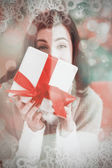Brunette showing gift on the couch — Stock Photo