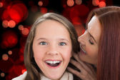 Composite image of mother and daughter telling secrets — Stock Photo