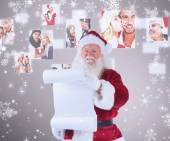 Father christmas holds a list — Stock Photo