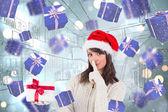 Composite image of festive brunette keeping a secret — Stock Photo