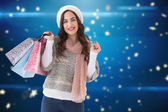 Composite image of brown hair in winter clothes holding shopping — Foto de Stock