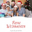 Extended family in christmas hats with gift — Stock Photo #62500843