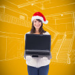 Brunette in santa hat showing her laptop — Stock Photo #62501019