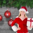 Festive blonde holding a gift — Stock Photo #62501095