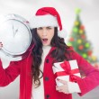 Surprised brunette holding a clock and gift — Stock Photo #62502197