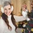 Smiling brunette holding a bauble at christmas — Stock Photo #62503779