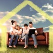 Happy family using the laptop in a field — Stock Photo #62504023