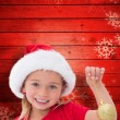 Composite image of cute little girl wearing santa hat holding ba — Stock Photo #62504491