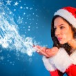 Pretty girl in santa outfit blowing — Stock Photo #62505663