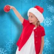 Composite image of cute little girl wearing santa hat holding ba — Stock Photo #62506017