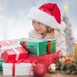 Composite image of cute little girl with gifts — Stock Photo #62507681