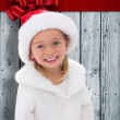 Composite image of cute little girl wearing santa hat — Stock Photo #62509495