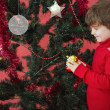 Festive little boy hanging bauble — Stock Photo #62509523