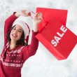 Composite image of pretty brunette showing sale bag and shopping — Stock Photo #62509631