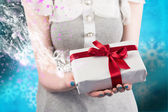 Woman offering a wrapped gift — Stock Photo