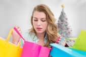 Composite image of blonde woman opening gift bag and looking on  — Stock Photo