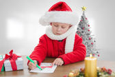 Composite image of cute boy drawing festive pictures  — Zdjęcie stockowe
