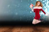 Festive redhead jumping with gift — Stock Photo