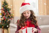Festive little girl opening gift — Stock Photo