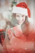 Festive brunette pressing gift at christmas — Foto de Stock