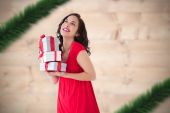 Composite image of stylish brunette in red dress holding pile of — Stockfoto