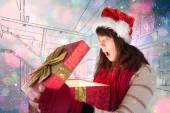 Festive brunette opening a gift — Stock Photo