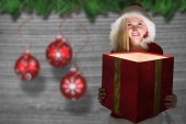 Festive blonde looking into glowing gift — Stock Photo