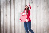 Composite image of happy brunette holding many gifts — Photo