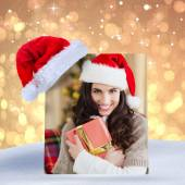 Composite image of festive brunette pressing gift at christmas — Stock Photo