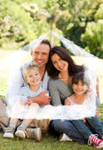 Composite image of family sitting in the park — Stock Photo