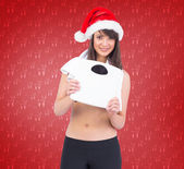 Festive fit brunette holding a weighing scales — Stock Photo