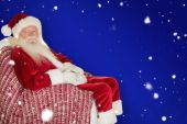 Smiling santa relaxing on armchair — Stockfoto