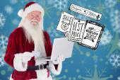 Santa pays with credit card on laptop — Stock Photo