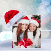 Composite image of festive mother and daughter smiling at camera — Stock Photo