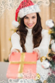 Surprised brunette showing a gift — Stock Photo