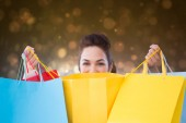 Composite image of happy brunette opening shopping bags — Stock Photo