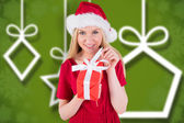 Composite image of festive blonde in red dress opening a gift — Stock Photo