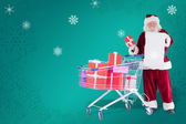 Santa spread presents with shopping cart — Stock Photo