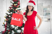 Composite image of stylish brunette in red dress showing sale ba — Zdjęcie stockowe