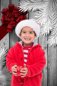 Composite image of cute little boy holding bauble — Stock Photo