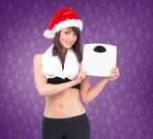 Festive fit brunette holding weighing scales — Stock Photo