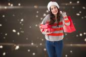 Composite image of smiling brunette holding gifts and showing sh — Stock Photo