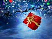 Santa flying behind big gift — Stockfoto