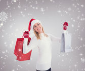 Festive blonde holding christmas gifts — Stock Photo